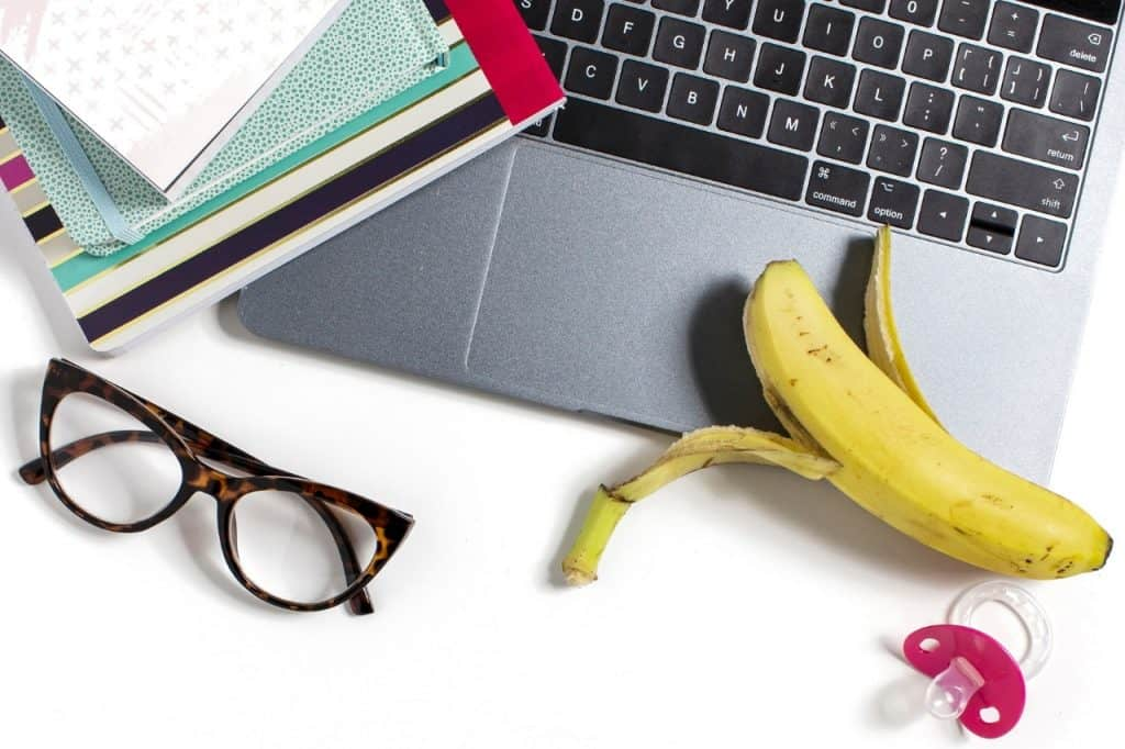 Glasses, laptop, binkie, banana, and planners