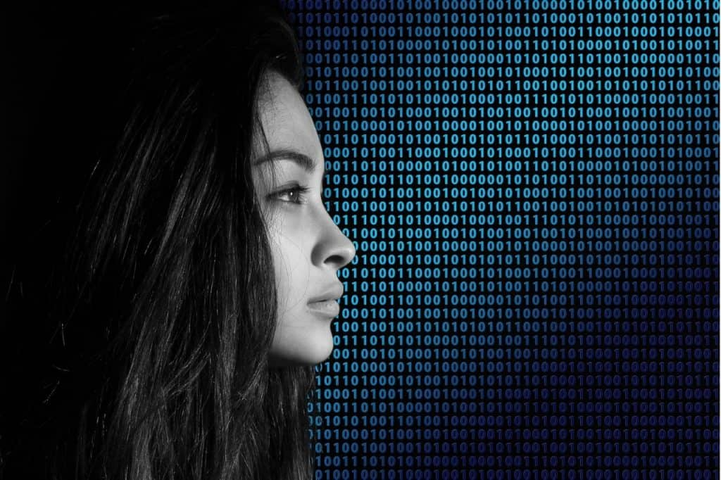 Woman's face over a dark screen with scrolling HTML code