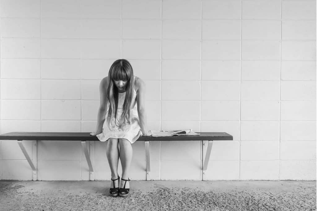 Black and white image of woman sitting alone looking tired